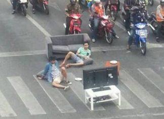 大渋滞の交差点でテレビ鑑賞をする二人のタイ人