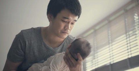 泣きやむ赤ちゃんを見る夫