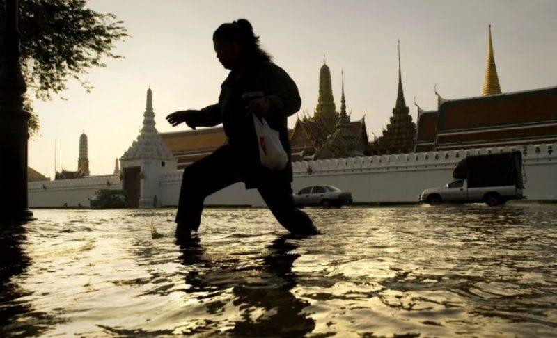 浸水する道路をまたぐ女性